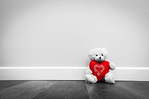 Teddy bear with red plush heart.