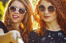 Two girls making fun selfie.