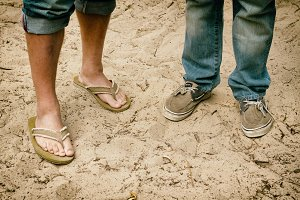 gay couple, feet in sand, engaged