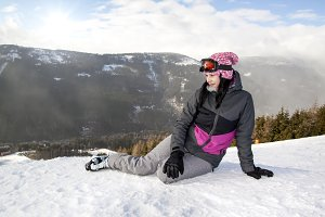 Girl skier lying on snow in mountain