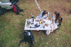 Women looking road map in campsite