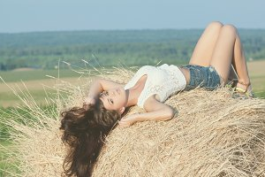 girl posing on a haystack