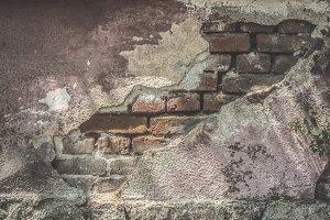 Broken plaster and brick wall