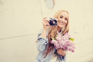 happy girl with a camera and lilac