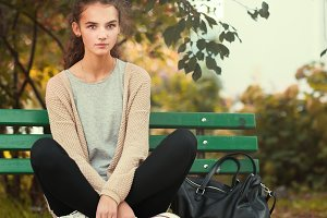 girl in sneakers sitting on a bench