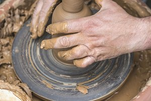 Potter makes clay bottle