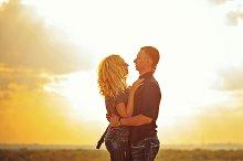 Loving couple hugging at sunset.