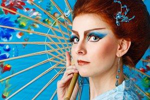 Geisha in smart dress with umbrella