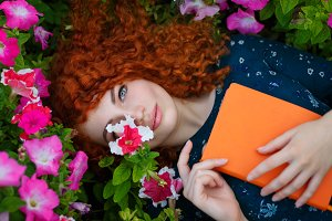Red-haired girl lies in wild flowers