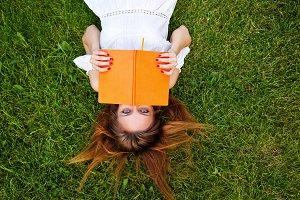 Girl reading book lying on lawn