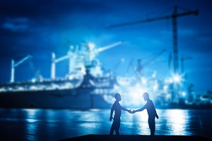 Business handshake in shipyard.