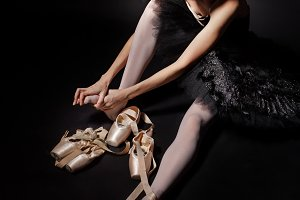 Ballerina tying pointe shoes.