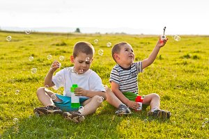 Boys blowing soap bubbles