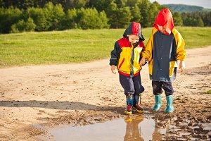 Two boys walking through a mud puddl