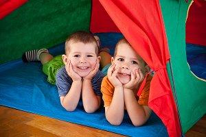 Little boys lying inside colorful te
