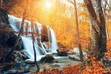 Waterfall at mountain river. Sunset