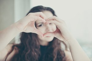 Young woman shows heart