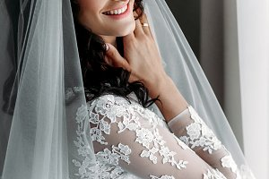 Smiling bride near the window