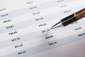 A pen pointing finance numbers