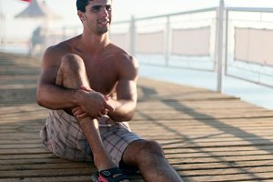 Young man sits on a pier