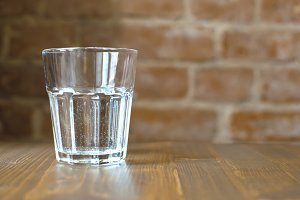 Glass of water and brick wall