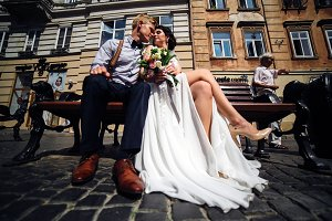 bride and groom sit on the bench