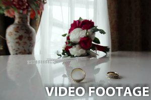 Rotating wedding rings near bouquet
