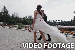 Newly married couple walk on park
