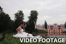 Bride and groom are sitting on grass
