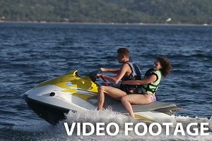 Happy couple riding jet ski.