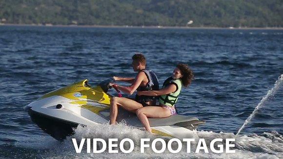 Happy couple riding jet ski.