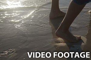 Legs walk on sand beach.