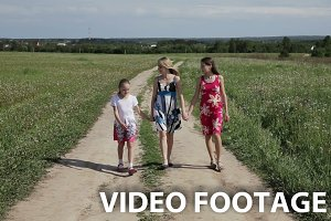 Mother with daughters walk on field