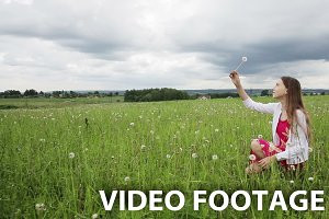 Young girl in field picks flower