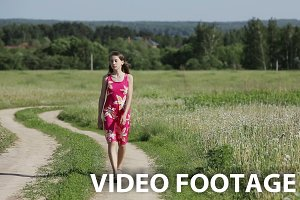 Girl walking by road in field