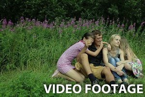 happy family four sitting on grass
