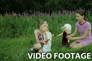 Girls play with dolls on grass