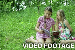 Two girls reading book
