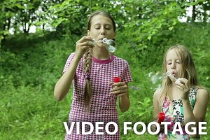Young girls blowing soap bubbles