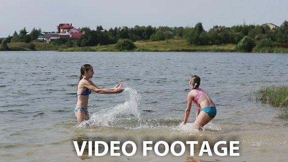 Girsl splashing in the lake.