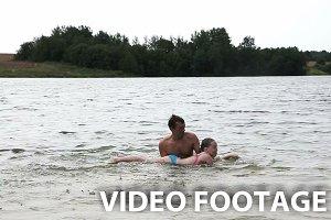 Man teaching girl how to swim.