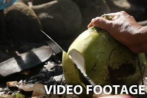 woman opening coconut with big knife