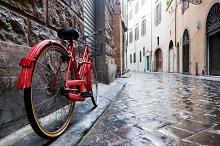 Red bike on cobblestone street.