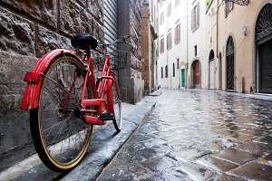 Red bike on cobblestone street.