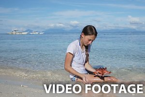 Girl playing with a starfish