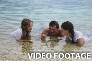 Father with daughters in the sea