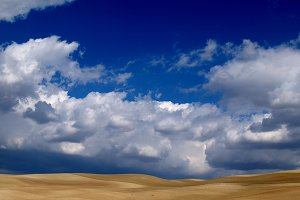 sky with clouds and desert field
