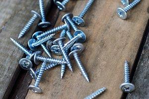 screws on old wooden desk close up