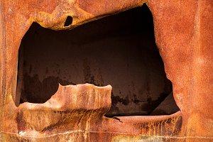 big hole in rusty steel plate