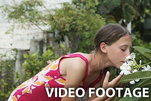 girl smelling  flower on branch